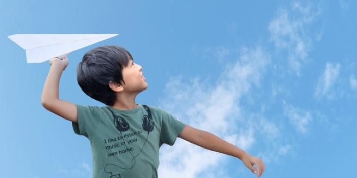 紙飛行機を飛ばす少年